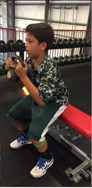 Small boy undergoing strength training