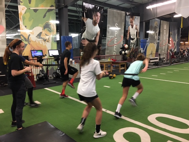 Boys and girls practicing running at a gym